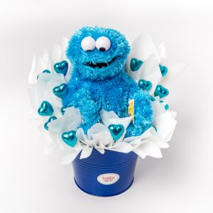A 25cm Sesame Street Cookie Monster and 15 blue foil wrapped milk chocolate hearts surrounded by white cello in a keepsake large blue metal bucket.