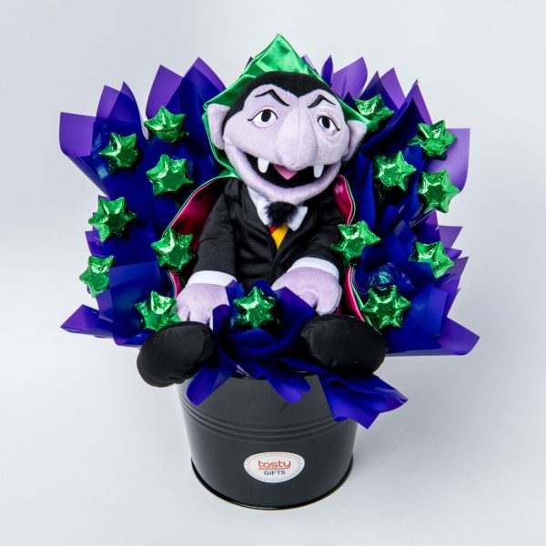 A 36cm Sesame Street Count von Count soft toy and 15 green foil wrapped milk chocolate stars surrounded by purple cello in a keepsake large black metal bucket.