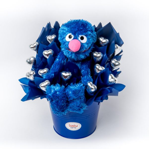 A 30cm Sesame Street Grover soft toy and 15 Silver foil wrapped milk chocolate hearts surrounded by royal blue cello in a large keepsake metal bucket.