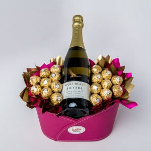 A 750ml Wolf Blass Bilyara Sparkling NV and 18 Ferrero Rocher chocolates surrounded by pink and gold cello in a pink leather look keepsake tub.