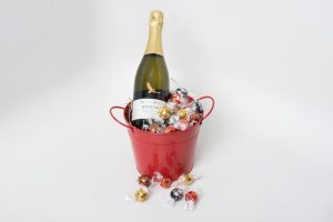 A 750ml bottle of Wolf Blass Bilyara sparkling brut NV surrounded by 12 Lindt chocolate balls. All wrapped up in a large red keepsake metal bucket.