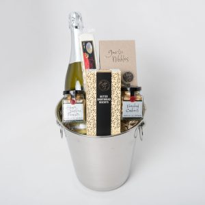 A 750ml bottle of Stony Peak sparkling brut NV surrounded by gourmet Ogilvie & Co. and Flying Swan products. All wrapped up in a keepsake stainless steel champagne ice bucket.