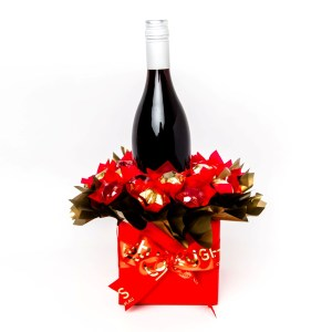 A 750ml bottle of Stony Peak red wine with 20 red and gold foil wrapped milk chocolate stars, surrounded by red and gold cello in a small black box. Finished with a red ribbon with gold print.