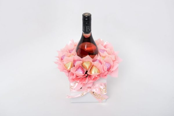 A 750ml Brown Brothers Moscato Rosé with 20 pink and gold foil-wrapped milk chocolate hearts, surrounded by baby pink cello in a small white box.