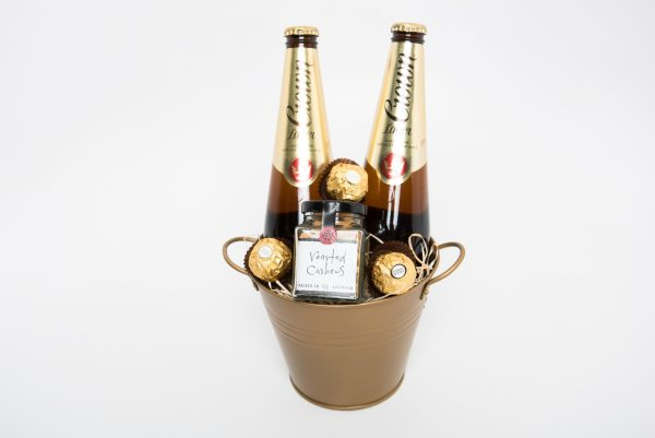 2 Crown lagers, a 60g Ogilvie & Co. roasted nuts and 3 Ferrero Rocher chocolates presented in a small gold keepsake bucket.