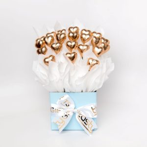 22 rose gold foil wrapped milk chocolate hearts surrounded by white cello in a small baby blue box.
