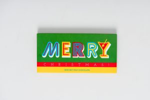 """A Bloomsberry 100g """"Merry Christmas"""" milk chocolate bar and 16 gold foil wrapped milk chocolate stars surrounded by red cello in a lime green box. Finished with a red ribbon with gold print."""