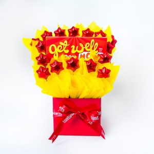 """A 100g Bloomsberry """"Get Well Soon"""" milk chocolate bar and 16 red foil wrapped milk stars surrounded by yellow cello in a small red box."""
