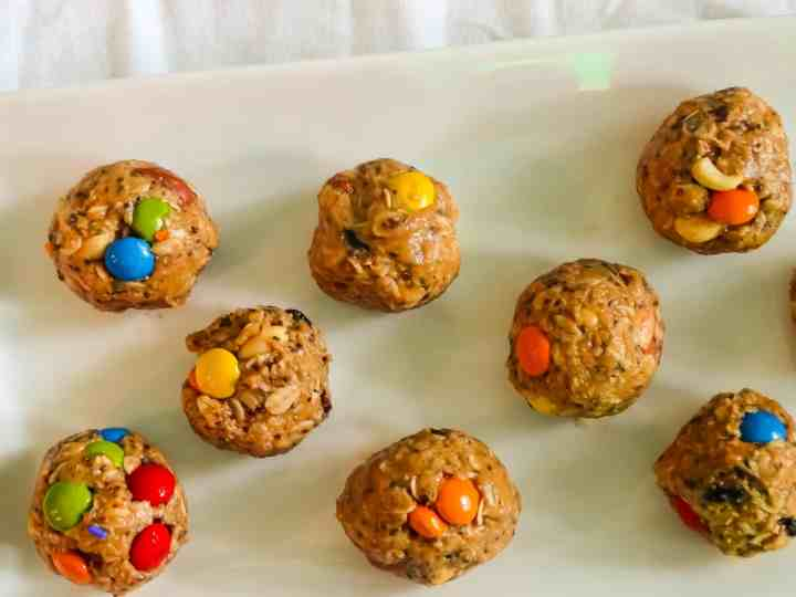 "alt=""trail mix energy balls with peanut butter, oats, and m&ms in rows on a white serving plate"""