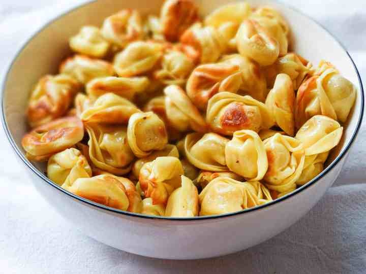 pan fried tortellini in a large white bowl
