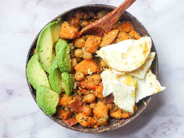sweet potato chickpea hash with avocado and egg in a coconut bowl