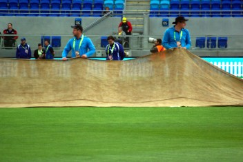 Grounds staff cover the wicket with hessian during a light shower.
