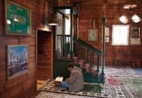 Хранитель и гид по мечети в Крушинянах Джемиль Гембицки с Кораном перед деревянным михрабом