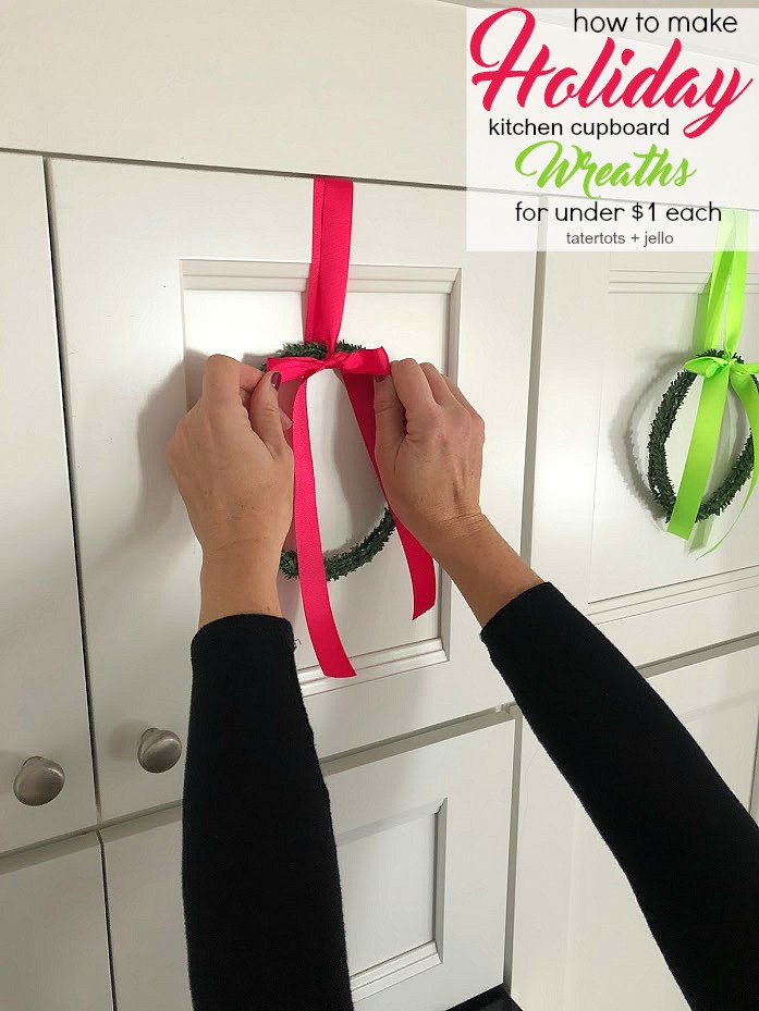 How to make mini cupboard wreaths for a dollar. Make mini wreaths out of tiny rolls of garland and hang them on your kitchen cupboards or on the back of chairs for the holidays.