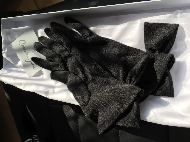 Black merino wool gloves with side bows in the white box