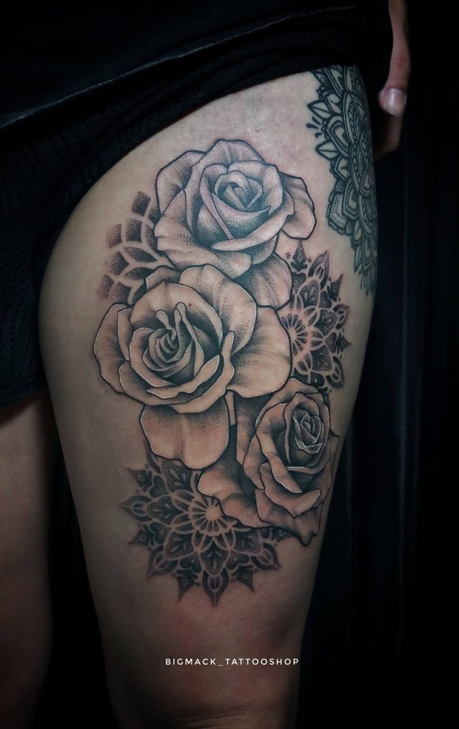 Thigh tattoo of three big rose blossoms lined with grey or black ink with inverted dotwork mandalas behind them. Tattooed by artist Dewa at Bigmack Tattoo Shop. Bali, 2018.
