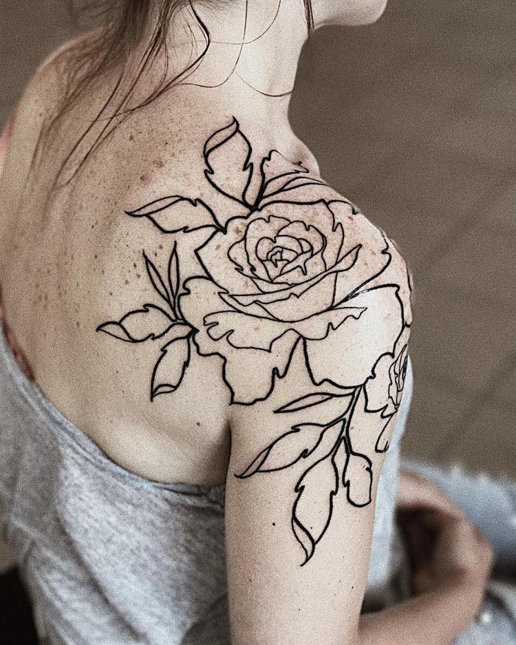 rose line tattoo on woman's shoulder