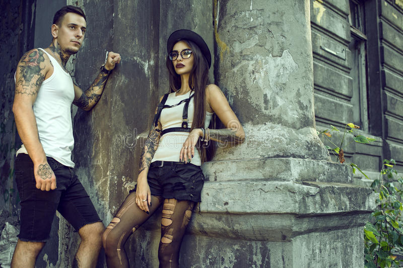 Young Stylish Tattooed Couple In Black Shorts Standing At Ideas And Designs