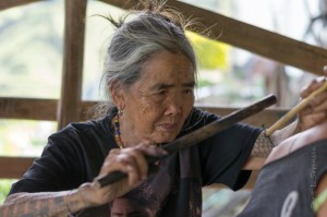Photo of Whang-od tattooing customer.
