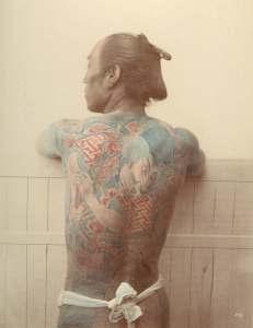 Efterhandsfärgat svartvitt foto. Tatuerad japansk samuraj visar upp tatuerad ryggtavla.