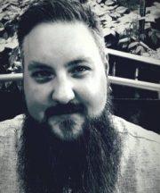 Svartvit porträttfoto av trettioårig man med kortklippt hår, skägg och mustasch.