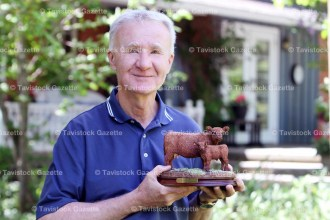 Dr. Brad Card stands with the Galloway cow and calf figurine that he received as a gift from the doctors and staff at Tavistock Community Health Inc. on his official retirement after 34 years serving the residents of Tavistock and area.