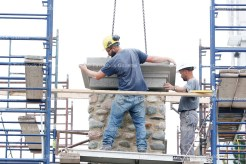 Stone masons Kyle and Robin Gilholm guide one of the caps on the top of the Queen's Park stone gates in Tavistock last week with the help of crane operator Brett Vanneste of Stratford Crane Rental. More work is still to be done before the job is complete.