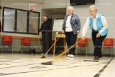 Katherine Roth slides her puck across the floor while playing with partner Joyce Zehr. Behind is scorekeeper Ken Ruby.