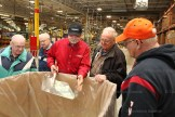C.R. Plastic Products' Bruce Ballantyne (centre) shows the ground, recycled plastics used at the outdoor furniture plant in Stratford.