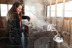 Larissa Brenneman skims impurities from the evaporator in their sugar shack.