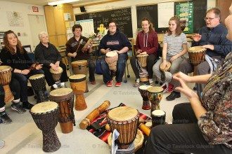 Sprucedale teacher Tarra Green (right) leads a drum circle at the school last Thursday evening to raise funds for the playground.