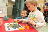 Kindergarten student Logan Nahrgang plays a leprechaun version of roll and cover with Noah Leis (behind) and parent volunteer Jenn Zehr helping them add and count the numbers on their dice.