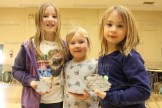 Glaab sisters Ava, 9, Teagan, 5, and Analise, 7, show off their clay imprints during the March Break Camp Alliwannado held in the Memorial Hall last week.