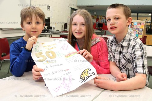 Tavistock Public School student Reegan Ziegler (centre) displays her poster advertising the 50th Anniversary Celebration for Tavistock Public School to be held on Friday, May 5th, 2017. Grade 1 students Ben Church (left) and Dylan McCann and their class posted dozens of similar posters around the village last week.