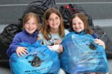 Grade 3 students, from the left, Emma Weitzel, Jenna McWhirter and Avery Brenneman hold some of the Bag2School donations that are being received this week at Tavistock Public School.