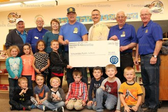 Optimist Club of Shakespeare members present a cheque for $5,000 to Sprucedale School Council Chair Heather Johnston to take the Playground Fundraising campaign over the goal of $100,000.