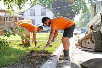 Hogg Construction, Thamesford, employees Mitchell Fitzmorris rakes out the ground as Jason Arts and Jake Elliott lay sod on the newly reconstructed Jacob Street East in Tavistock last Thursday morning.