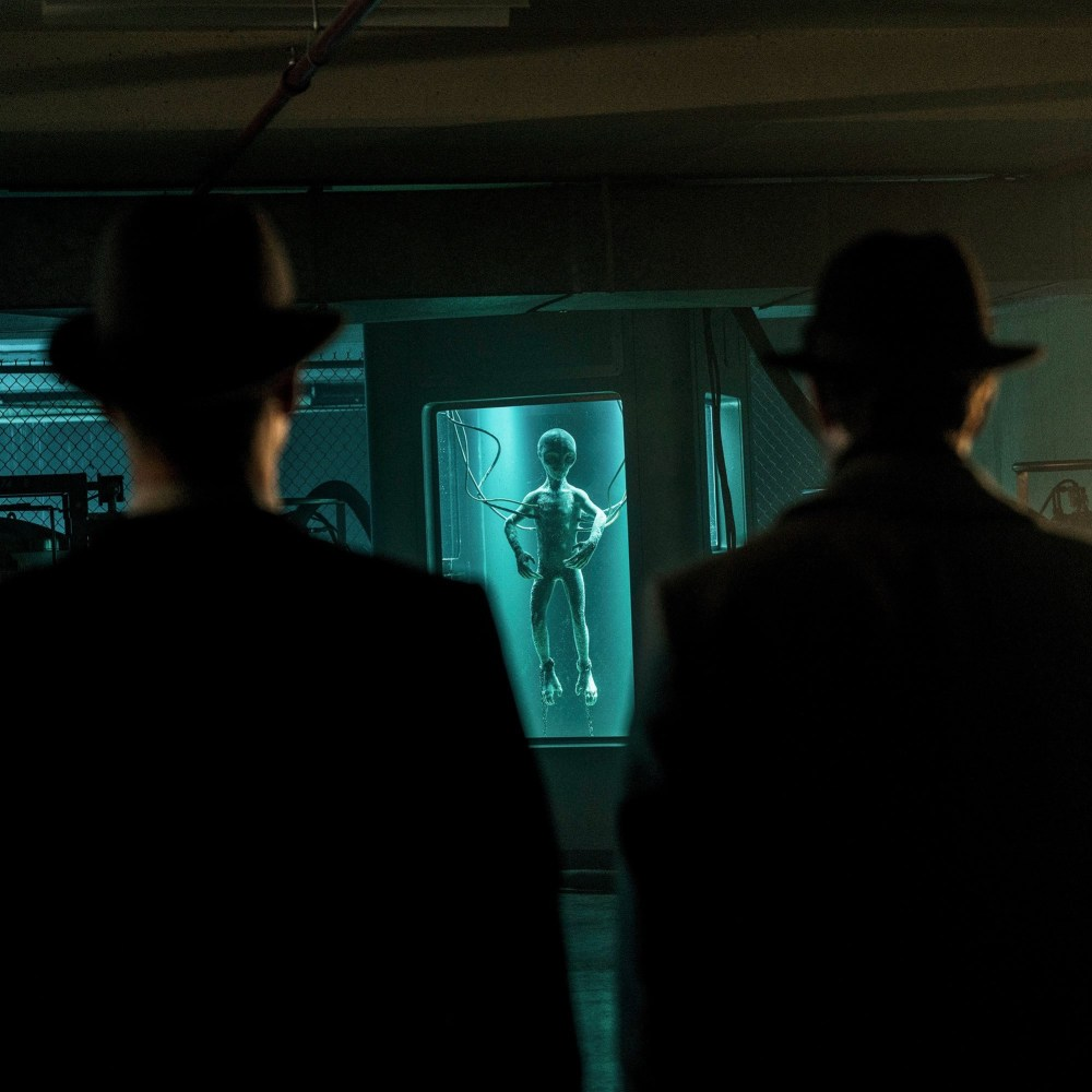 Men in hats in front of ET in a water tank
