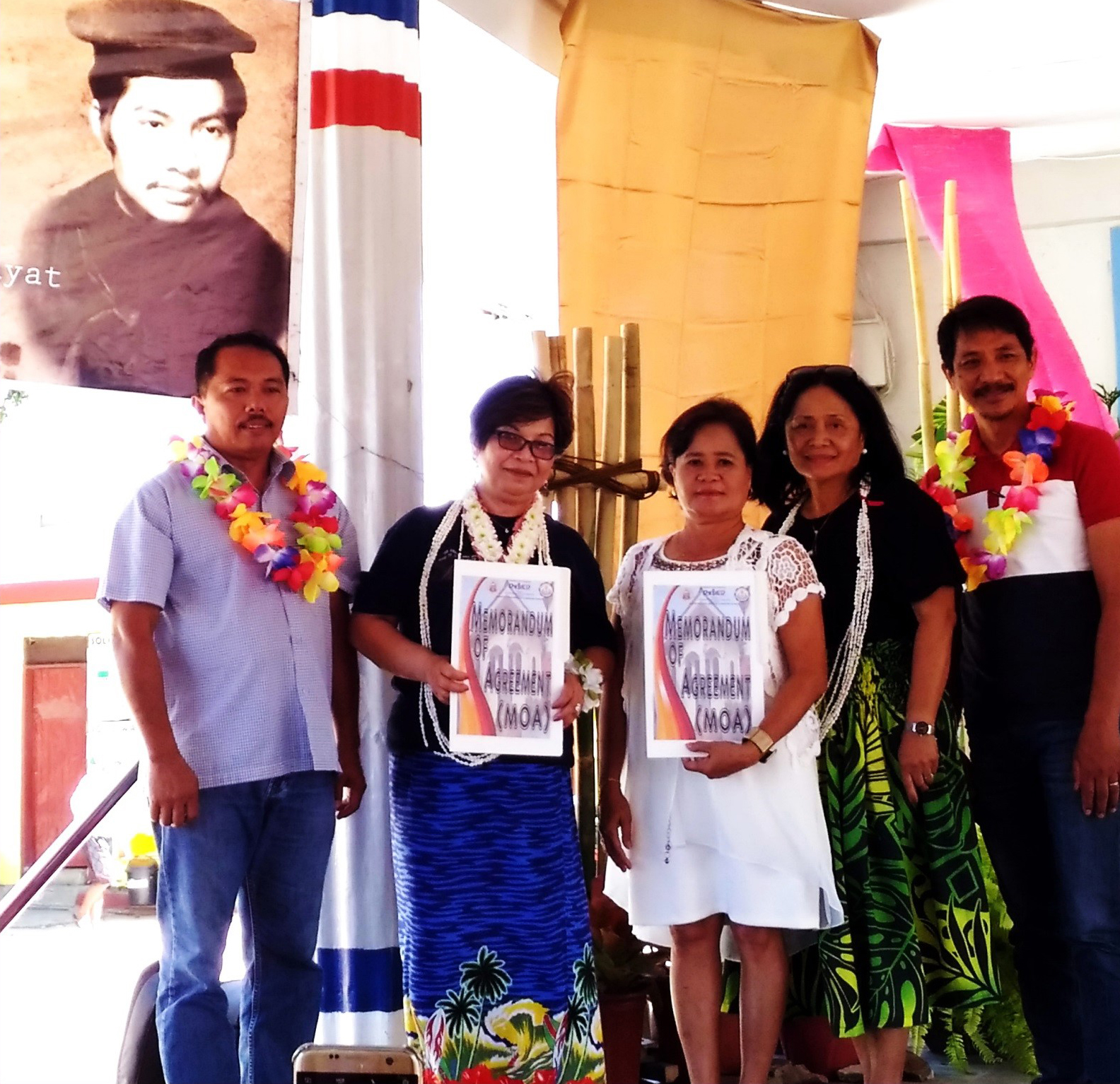 JENNY ALCAUSIN (2ND FROM LEFT) AND JULIANA PILA of Cabaroan-Cabalangegan Elem School (CCES) hold copies of the MOA as they pose for remembrance in front of the tarpaulined image of Mario Albalos, Feb. 2 at CCES in Cabaroan Laud, Vigan City. At left is Vigan City DepEd Superintendent Alselmo Aludino.