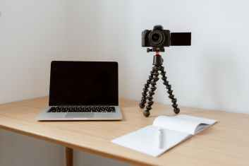 modern video camera and laptop near opened notebook