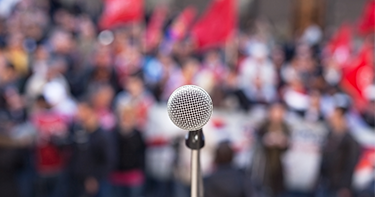 image of a microphone in front of a protesting crowd