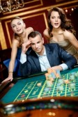 Man with two girls playing-roulette