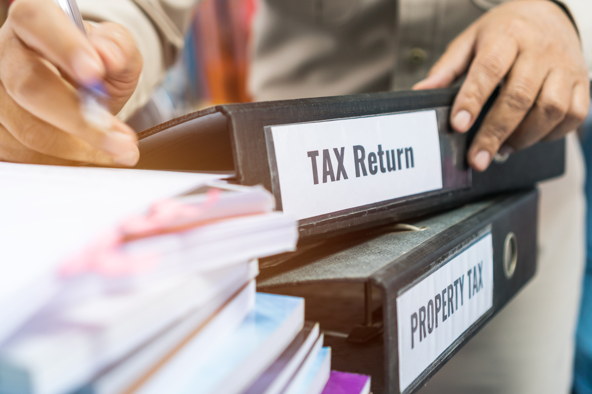 Tax return and property tax folders stack with label black binder on paperwork documents summary report in busy offices by manager checking. HR-human resources business bookkeeping accountancy Concept