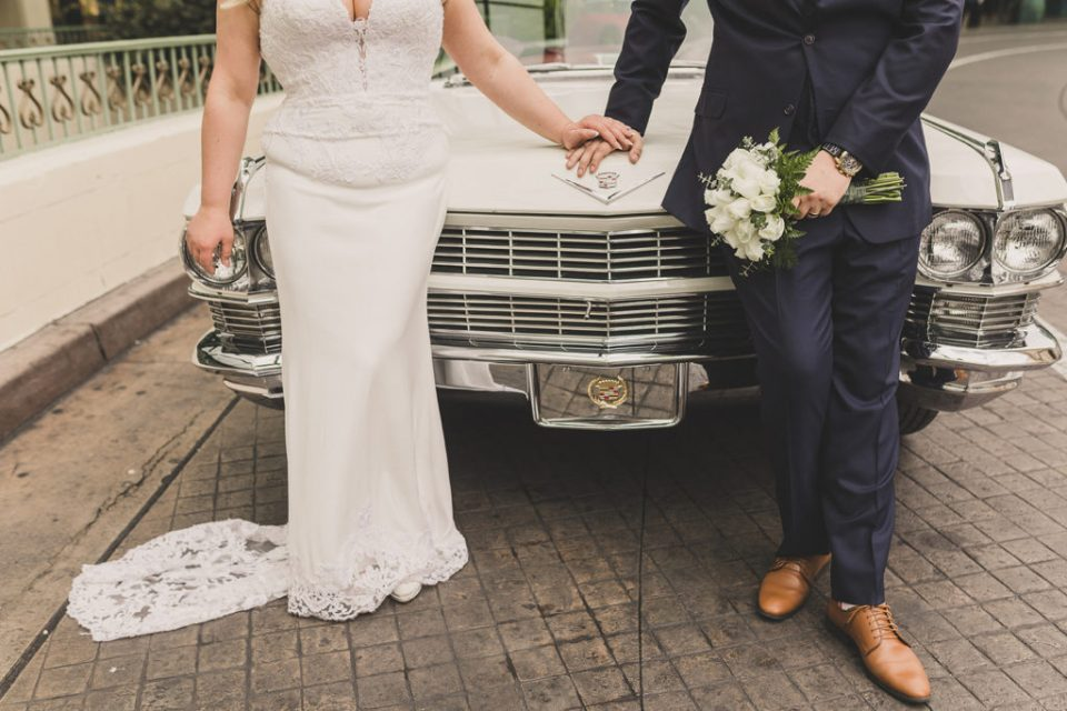 bride and groom pose by white Cadillac on wedding day with Taylor Made Photography