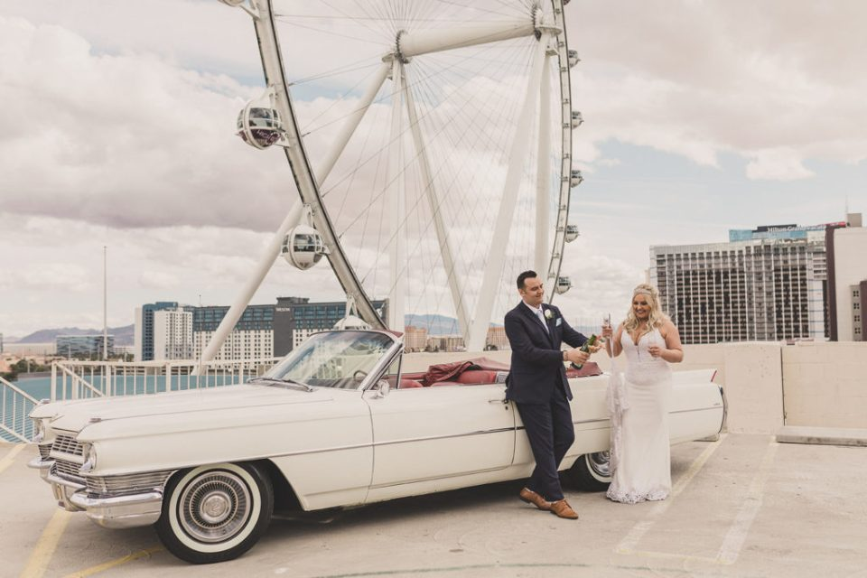 newlyweds have champagne toast by Cadillac in Las Vegas