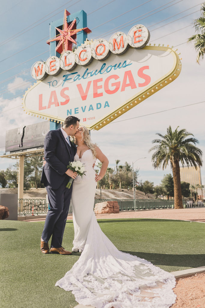 bride and groom pose by Las Vegas neon sign