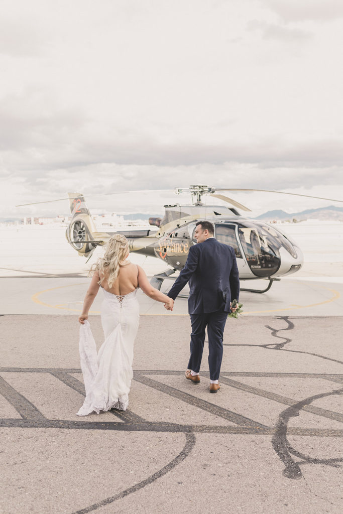 bride and groom walk to helicopter for elopement