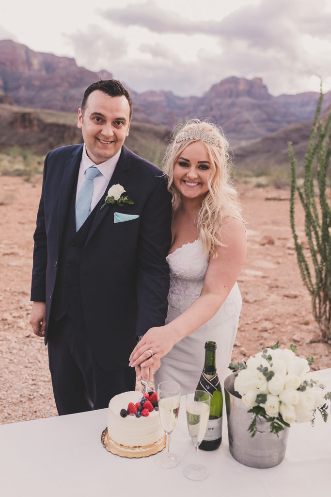 bride and groom cut cake during elopement in Grand Canyon
