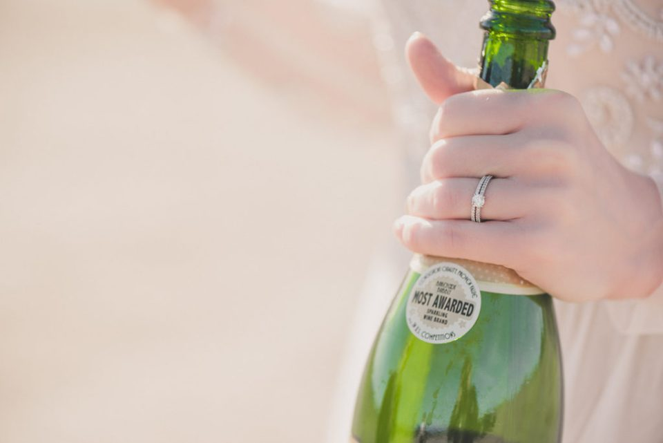 bride holds bottle of champagne photographed by Taylor Made Photography