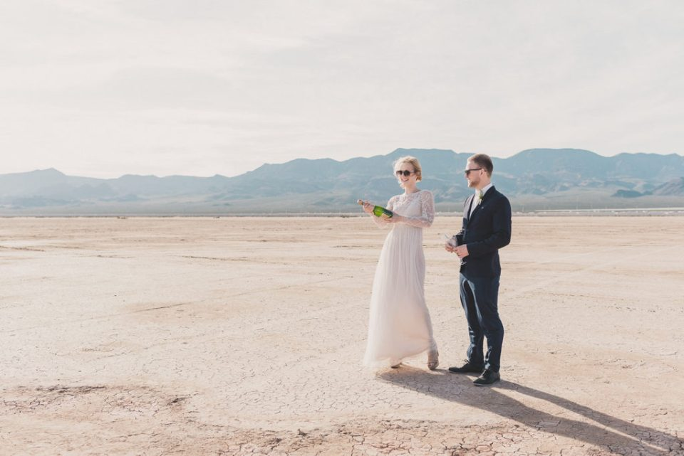 newlyweds pop champagne at El Dorado Dry Lake Bed photographed by Taylor Made Photography